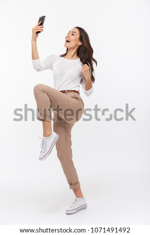 Full length portrait of a happy asian businesswoman celebrating with mobile phone isolated over white background