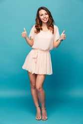 Full length portrait of a happy beautiful girl wearing dress showing thumbs up isolated over blue background