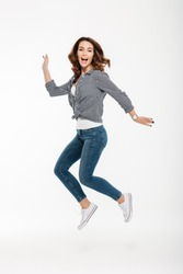 Full length portrait of a happy casual girl jumping isolated over white background