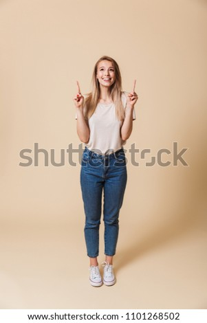 Full length portrait of a happy casual girl pointing finger up at copy space isolated over beige background