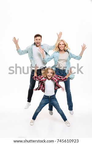 Full length portrait of a happy cheerful family with a child jumping together with outstretched hands isolated over white background #745610923