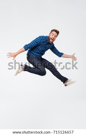 Full length portrait of a happy excited bearded man jumping and looking at camera isolated over white background #715126657