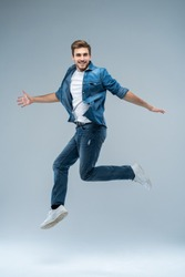 Full length portrait of a happy excited beardedman jumping and looking at camera isolated over grey background