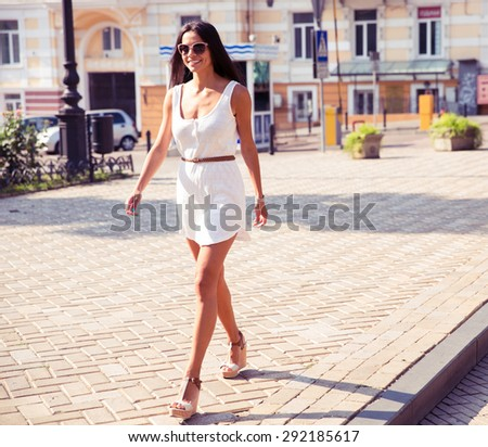 Full length portrait of a happy fashion woman walking in town