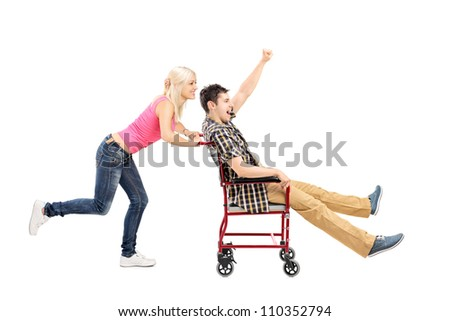 Full length portrait of a happy female pushing a man in wheelchair