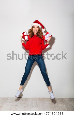 Full length portrait of a happy girl dressed in red sweater and christmas hat holding gift box while jumping and looking at camera isolated over white background stock photo