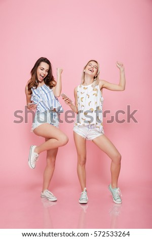 Full length portrait of a happy girlfriends dancing and having fun while listening to music isolated on the pink background