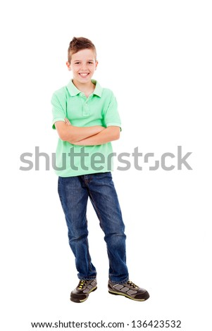 Full length portrait of a happy little boy standing with folded arms over white background