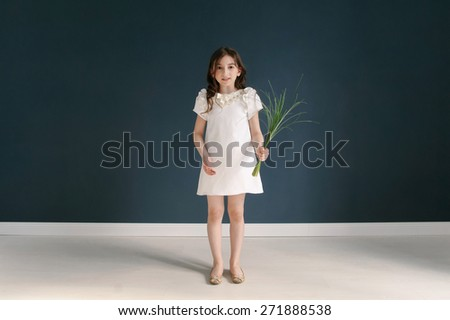 Full length portrait of a happy little girl on dark background.