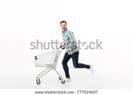Full length portrait of a happy man running with a shopping trolley isolated over white background