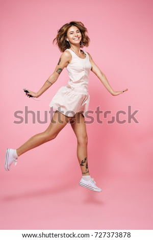 Full length portrait of a happy smiling girl in summer dress in earphones listening to music while holding mobile phone and jumping isolated over pink background