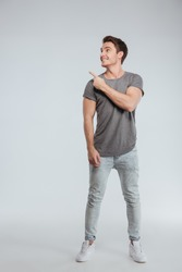Full length portrait of a happy smiling man pointing finger away at copyspace isolated on a white background