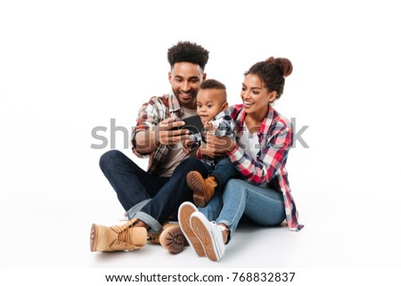 Full length portrait of a happy young african family with their little son taking a selfie while sitting together isolated over white background #768832837
