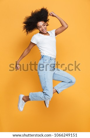 Full length portrait of a happy young african woman celebrating success while jumping isolated over yellow background #1066249151