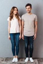 Full length portrait of a happy young couple standing and looking at each other over gray wall