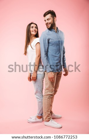 Full length portrait of a happy young couple standing back to back isolated over pink background