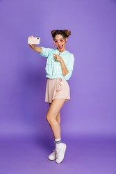 Full length portrait of a happy young girl with bright makeup over violet background, posing while standing, taking a selfie, pointing finger