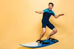 Full length portrait of a happy young man dressed in swimsuit surfing on a board isolated over yellow background