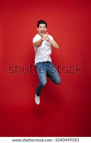 Full length portrait of a happy young man in white t-shirt pointing fingers at camera while celebrating success isolated over red background
