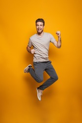 Full length portrait of a happy young man jumping and celebrating success isolated over yellow background