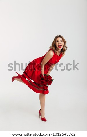 c02adc4f1 Full length portrait of a happy young woman dressed in red dress holding  bouquet of roses