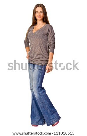 Full length portrait of a happy young woman standing against white background - stock photo
