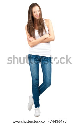 Full length portrait of a happy young woman standing with folded hand against white background
