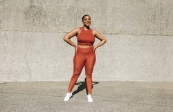 Full length portrait of a healthy woman standing outdoors. Female in sportswear standing with hands on hips looking at camera and smiling.