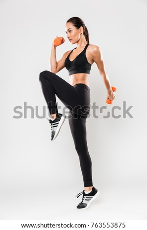 Full length portrait of a healthy young asian fitness woman doing exercises with dumbbells isolated over white background