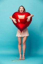 Full length portrait of a joyful beautiful girl wearing dress standing and holding heart shaped balloon isolated over blue background