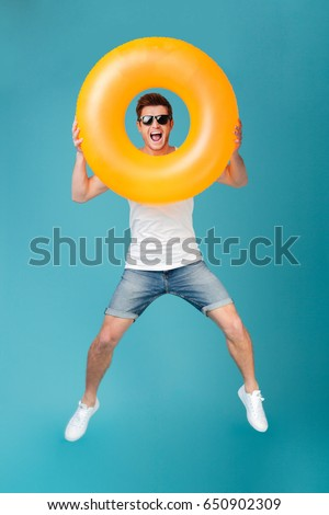 Full length portrait of a joyful happy guy in sunglasses jumping and looking through inflatable ring isolated over blue background