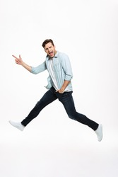 Full length portrait of a joyful happy man jumping and pointing finger away isolated over white background