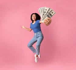 Full length portrait of a joyful young asian woman jumping up high and holding bunch of money banknotes, showing close to camera, celebrating win, isolated over pink studio background, collage