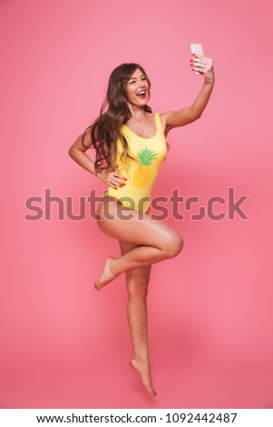 Full length portrait of a joyful young woman dressed in swimsuit taking selfie with mobile phone while jumping isolated over pink background