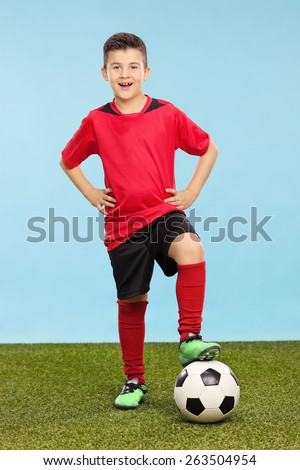 Full length portrait of a junior in a soccer uniform standing over a soccer ball on a grass field with a blue background