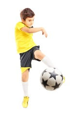 Full length portrait of a kid in sportswear shooting a soccer ball isolated on white background