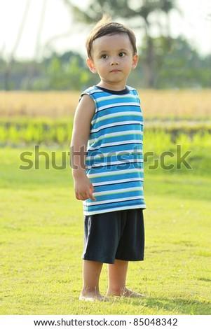 Full length portrait of a little boy standing in green field