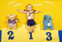 Full length portrait of a little child is standing on a place podium in first place. Handsome boy is cheering and standing on victory podium with medal. Funny baby. First place winner. Success concept