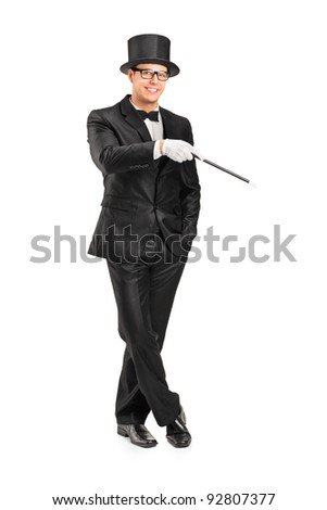 Full length portrait of a magician holding a magic wand posing isolated on white background