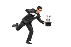 Full length portrait of a magician holding a top hat with a rabbit on it isolated on white background