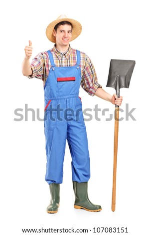 Full length portrait of a male agricultural worker holding a shovel and giving a thumb up isolated on white background