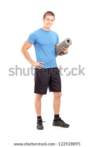 Full length portrait of a male athlete holding a mat isolated on white background