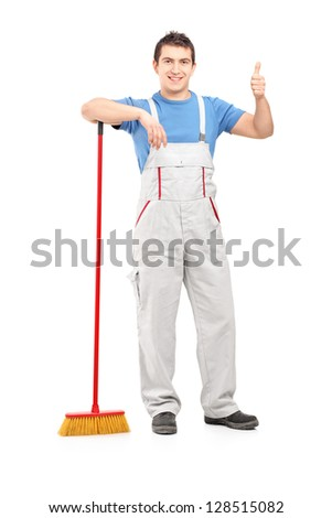 Full length portrait of a male cleaner with a broom giving thumb up isolated on white background