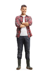Full length portrait of a male gardener in boots posing with crossed arms isolated on a white background