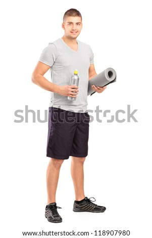 Full length portrait of a male holding a bottle of refreshment drink and a mat after an excerise isolated on white