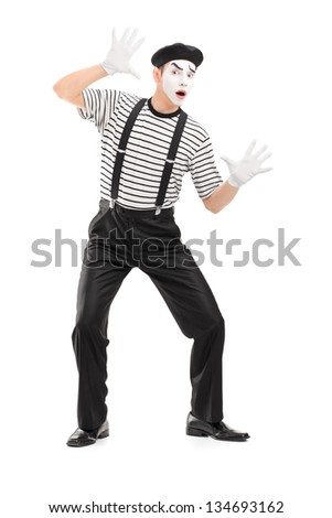 Full length portrait of a male mime artist performing, isolated on white background