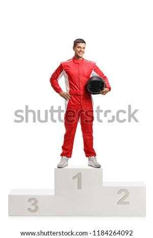 Full length portrait of a male racer winner on a winner's pedestal isolated on white background