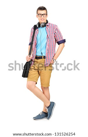 Full length portrait of a male student with a shoulder bag and headphones isolated on white background