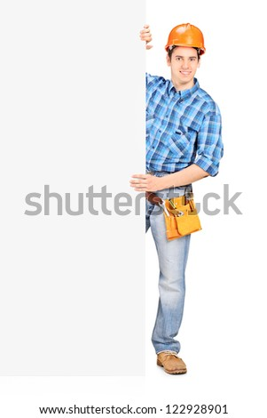 Full length portrait of a male worker with helmet posing behind a blank panel isolated on white background