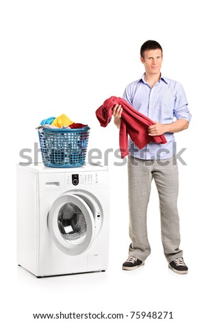 Full length portrait of a man holding a blouse and a washing machine isolated on white